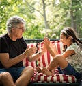 Elderly Man Playing A Clapping Game With His Granddaughter