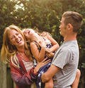 Happy Family Laughing Together In Their Backyard