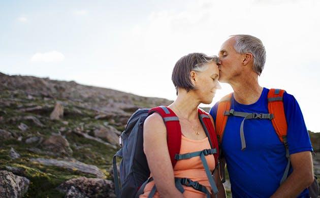 A CouMen kiss woman forehead  during a  Hikes Along A Mountain Trailple Kissing On A Mountain