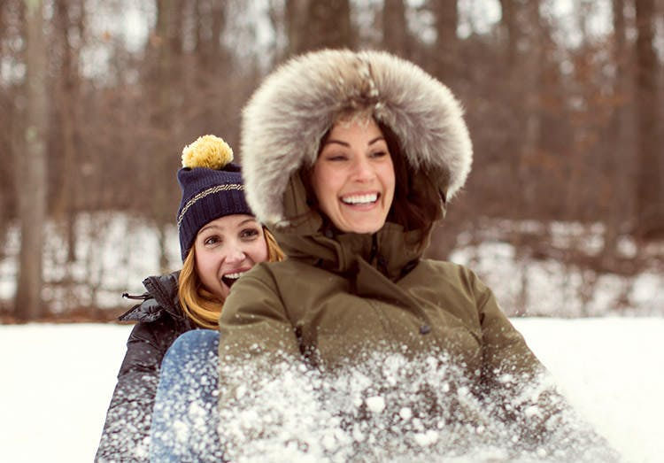 Two Women Having Fun Sledding In Woods