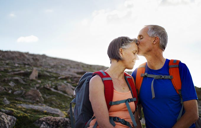 Men kiss woman forehead  during a  Hikes Along A Mountain Trail