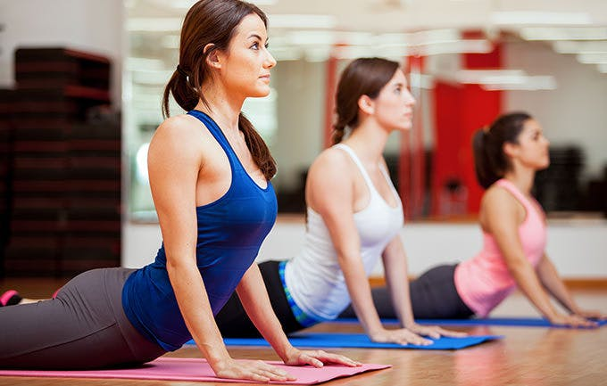 Hispanic Women Practicing The Cobra Pose During A Yoga Class