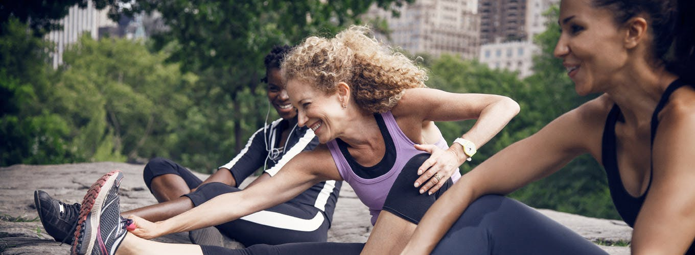 Three Friends In Exercise Gear Stretching