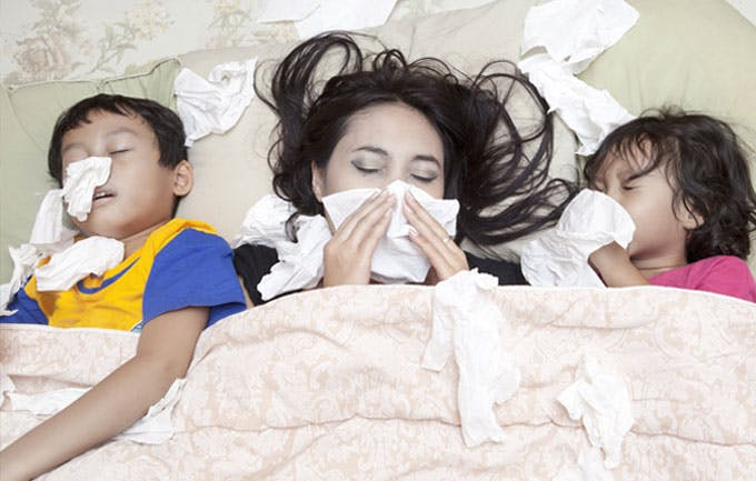 Mother, son and daughter sick in bed with flu