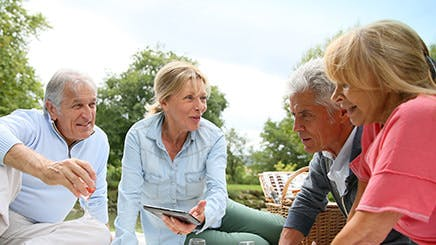 Dos parejas de adultos mayores compartiendo al aire libre.