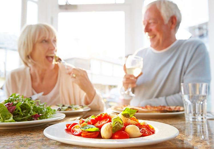 Pareja de adultos mayores tomando un almuerzo saludable.