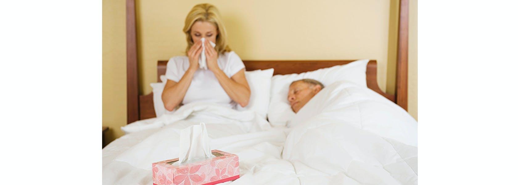 Pareja de adultos son sintomas gripales descansando en cama.