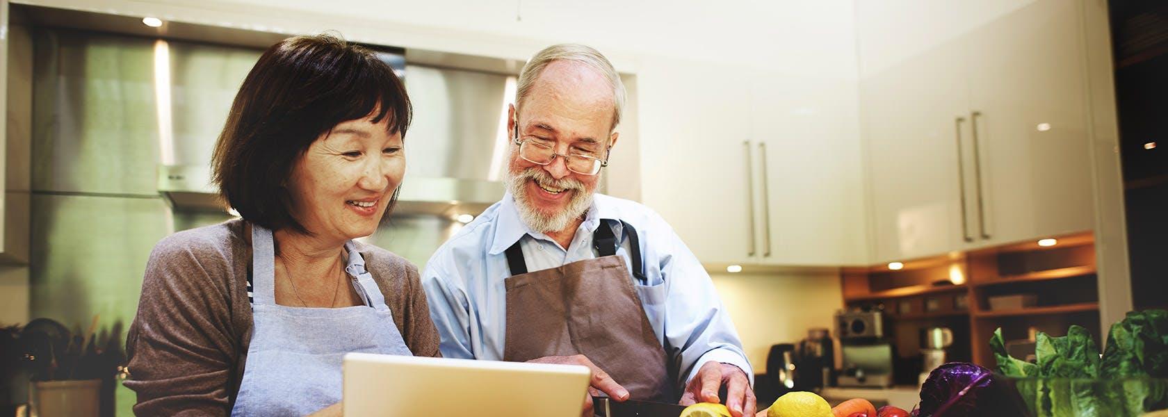 Pareja de adultos mayores preparando una receta.