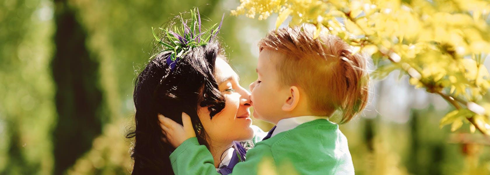 Madre e hijo al aire libre, el niño le esta dando un beso a la mamá en la nariz.
