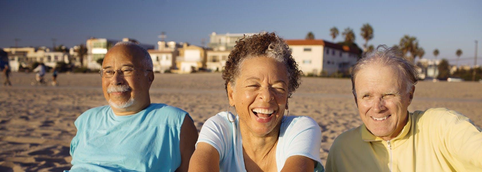 Tres adultos mayores toman el sol en una playa.