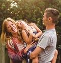 Una pareja de papás jóvenes juegan con su hija al aire libre.