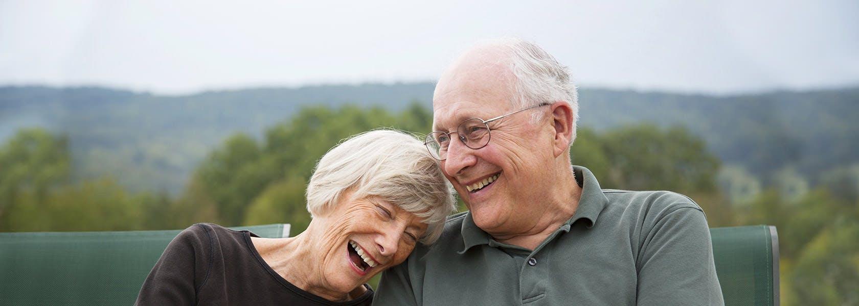 Una pareja de adultos mayores sonríen, sentados en un parque.