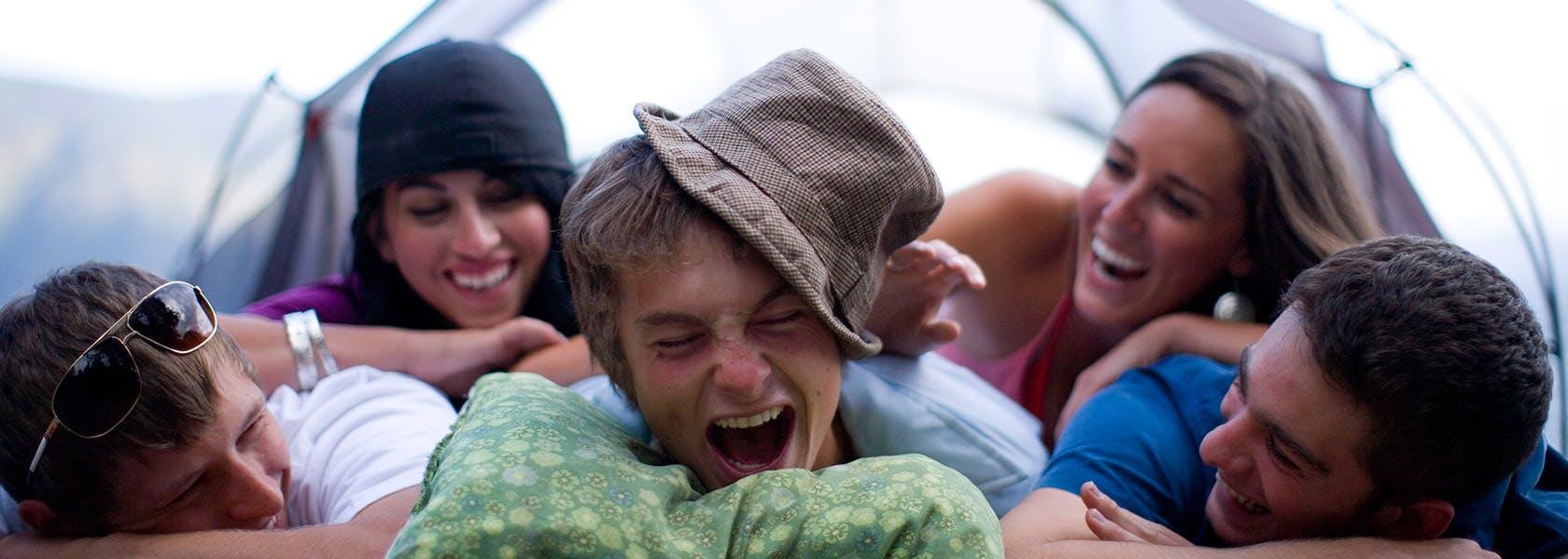 Grupo de amigos riendo en una carpa.