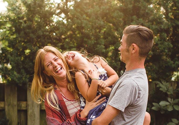 Pareja de padres jugando con su hija al aire libre.