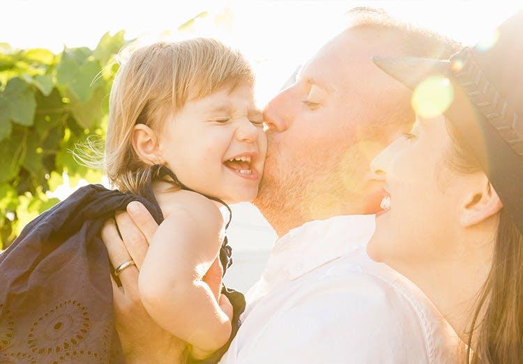 Padre alzando a su hija t dandole un beso mientras mamá sonrie