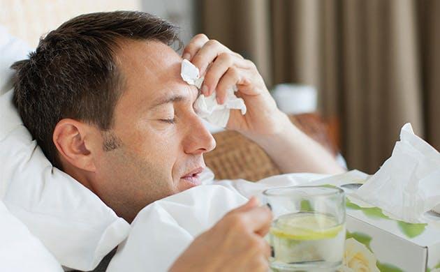 Hombre con sintomas gripales recostado en la cama tocandose la cabeza con señal de dolor