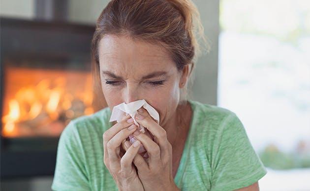 Mujer con síntomas gripales sonándose la nariz.