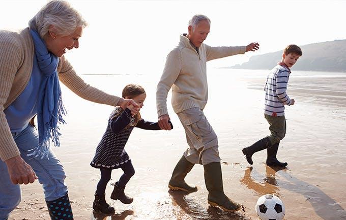 Abuelos jugando fútbol en la playa con sus nietos.