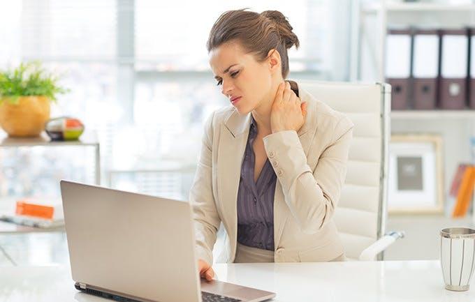 Mujer al frente de un computador portatil tocandose el cuello de dolor