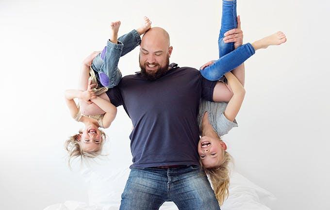Padre alzando boca a bajo a sus dos niñas