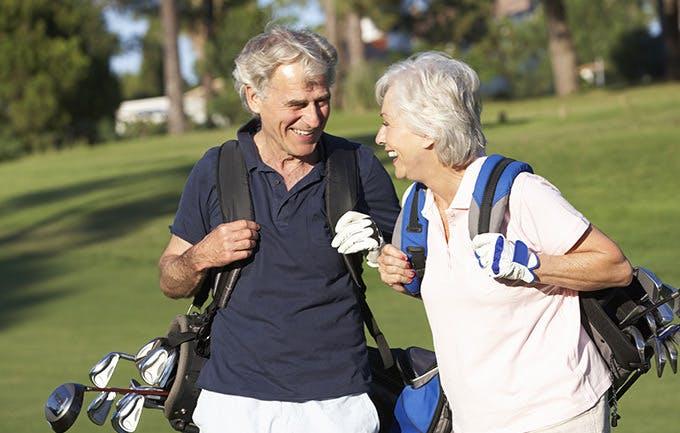 Pareja de adultos mayores jugando golf y sonriendo entre ellos.