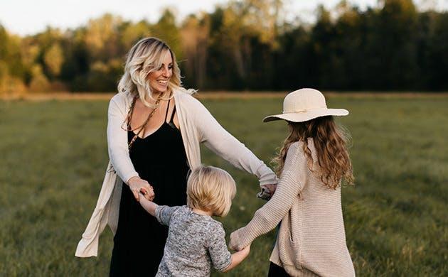 Madre e hijas baila en un campo