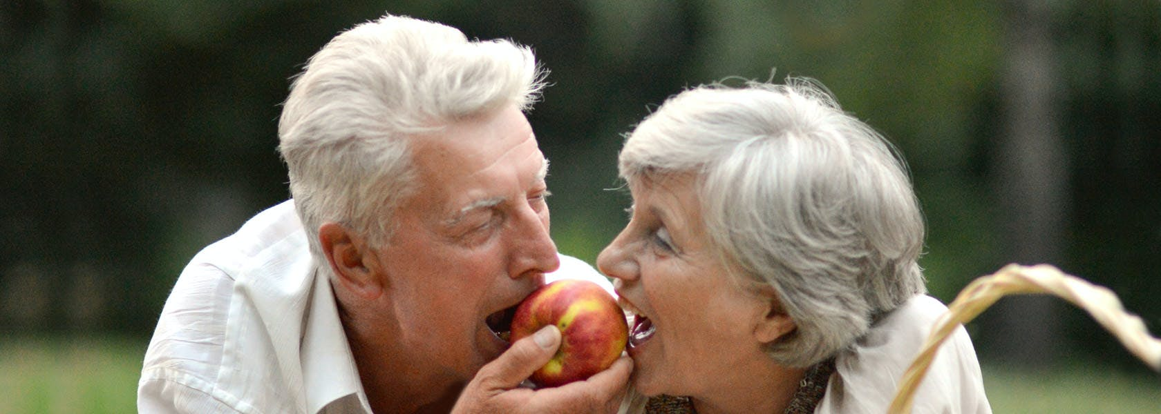 Pareja de adultos mayores comiendo una manzana y sonriendo