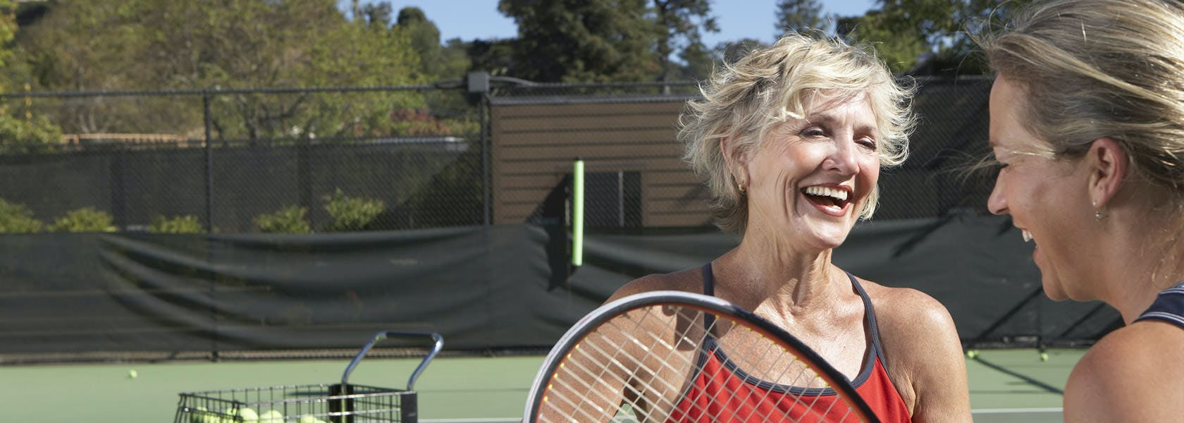 Dos mujeres conversando durante un partido de tennis