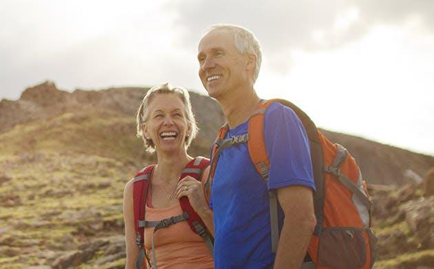 Una pareja disfruta y rie mientras  realiza  una caminata por la montaña
