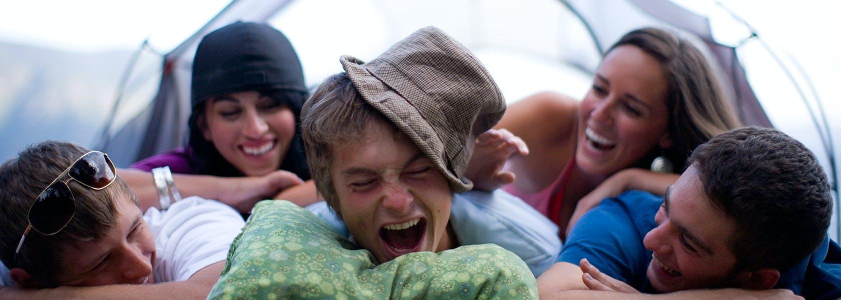 Amigos se ríen mientras se tirar sobre otro en un campamento