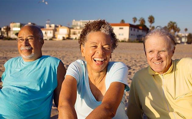 Tres adultos mayores relajandose en la playa