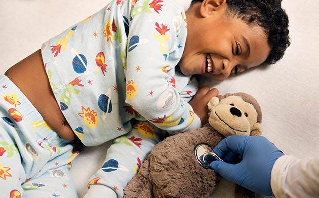 Un médico examinando al osito de peluche de un niño
