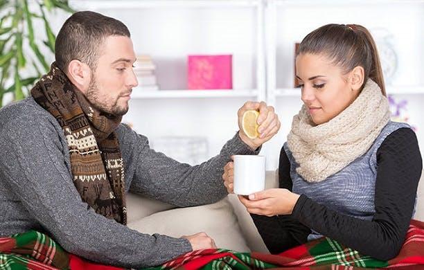 Hombre lleva un té caliente a una mujer resfriada