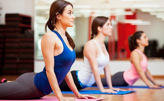 Hispanic Women Practicing The Cobra Pose During A Yoga Class