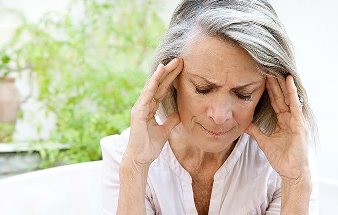 Mature Woman Touching Her Head With Her Hands