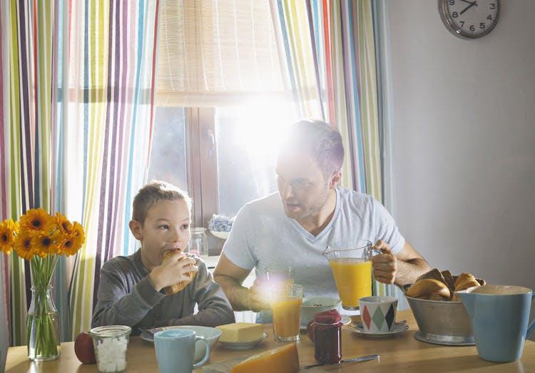 Ayah dan Anak Laki-Lakinya Duduk di Meja Makan untuk Sarapan