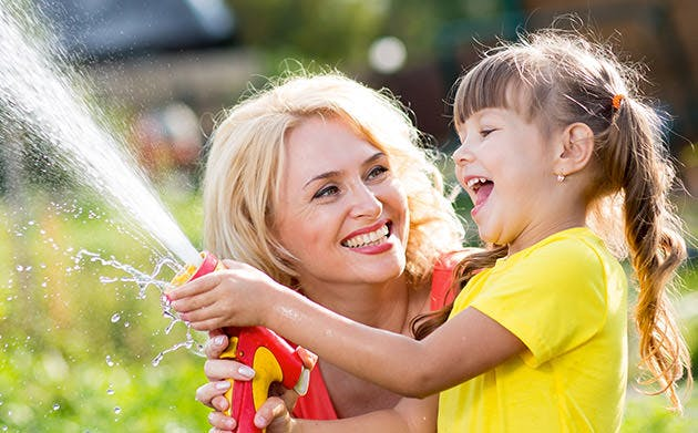 Happy Mother And Child Daughter Water In Domestic Garden