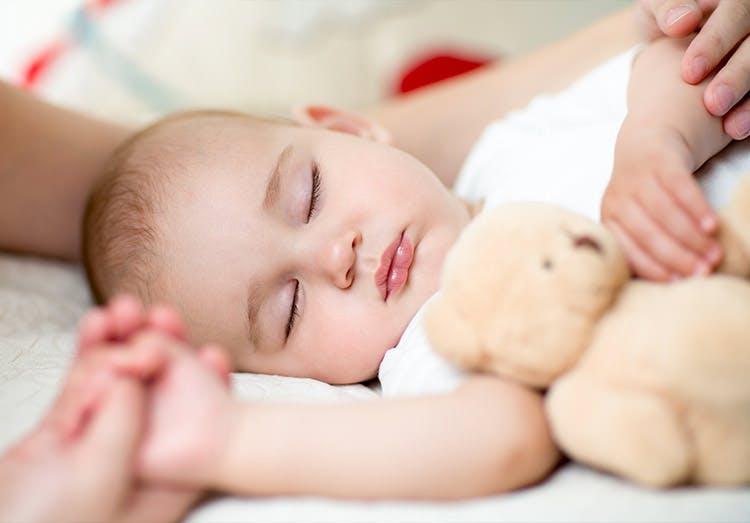 Bayi Laki-laki yang Lucu Tidur dengan Mainannya