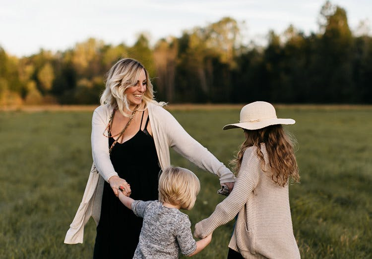 Mãe dança com as filhas ao ar livre