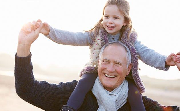 Avô passeia na praia com neta às cavalitas
