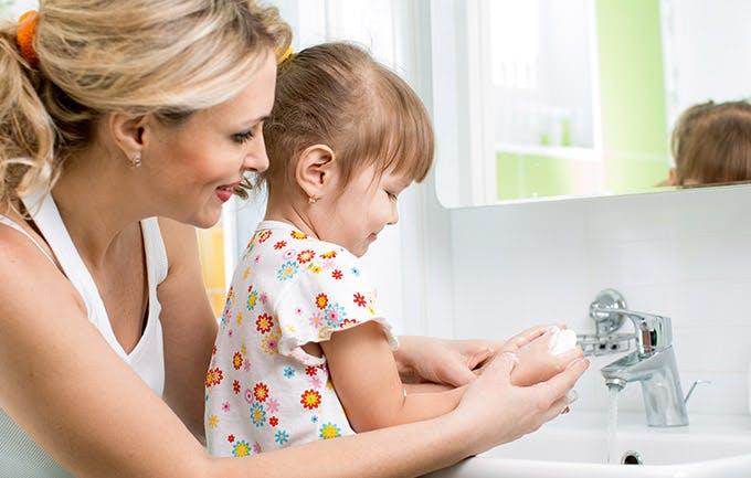 Criança lava as mãos com a sua mãe