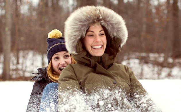 Two Women Having Fun Sledding In Woods