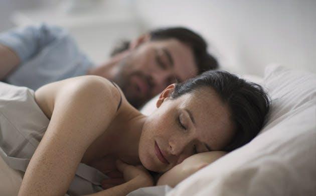 Cặp đôi ngủ trên giường vào buổi tối