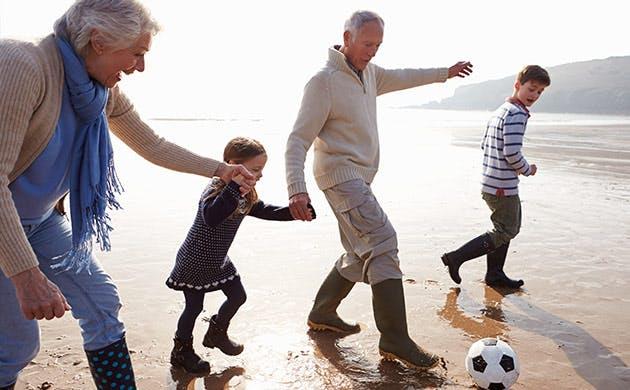 Ông bà và cháu chơi bóng trên bãi biển