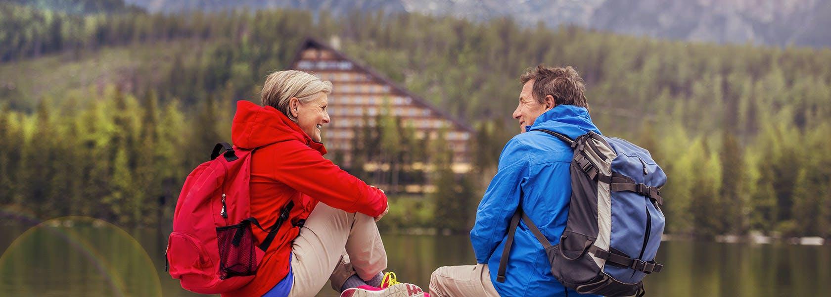 Cặp đôi trung niên đi bộ quanh hồ ở đồi núi đẹp