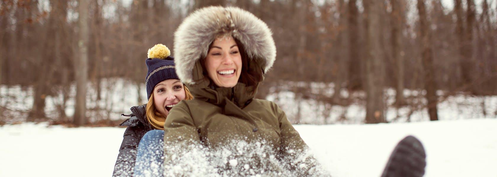 Hai phụ nữ đang chơi trượt tuyết bằng gỗ