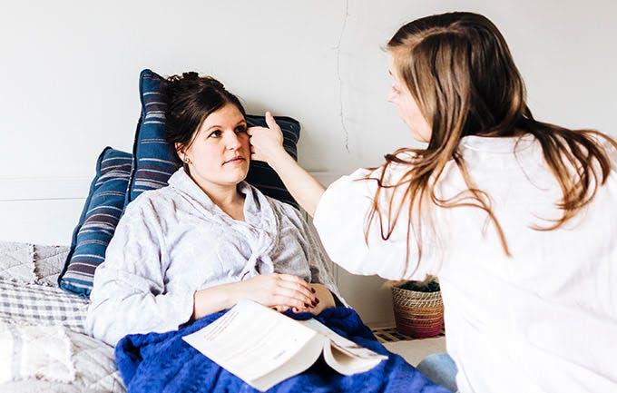 Bác sỹ dùng ống nghe khám bệnh cho phụ nữ trung niên