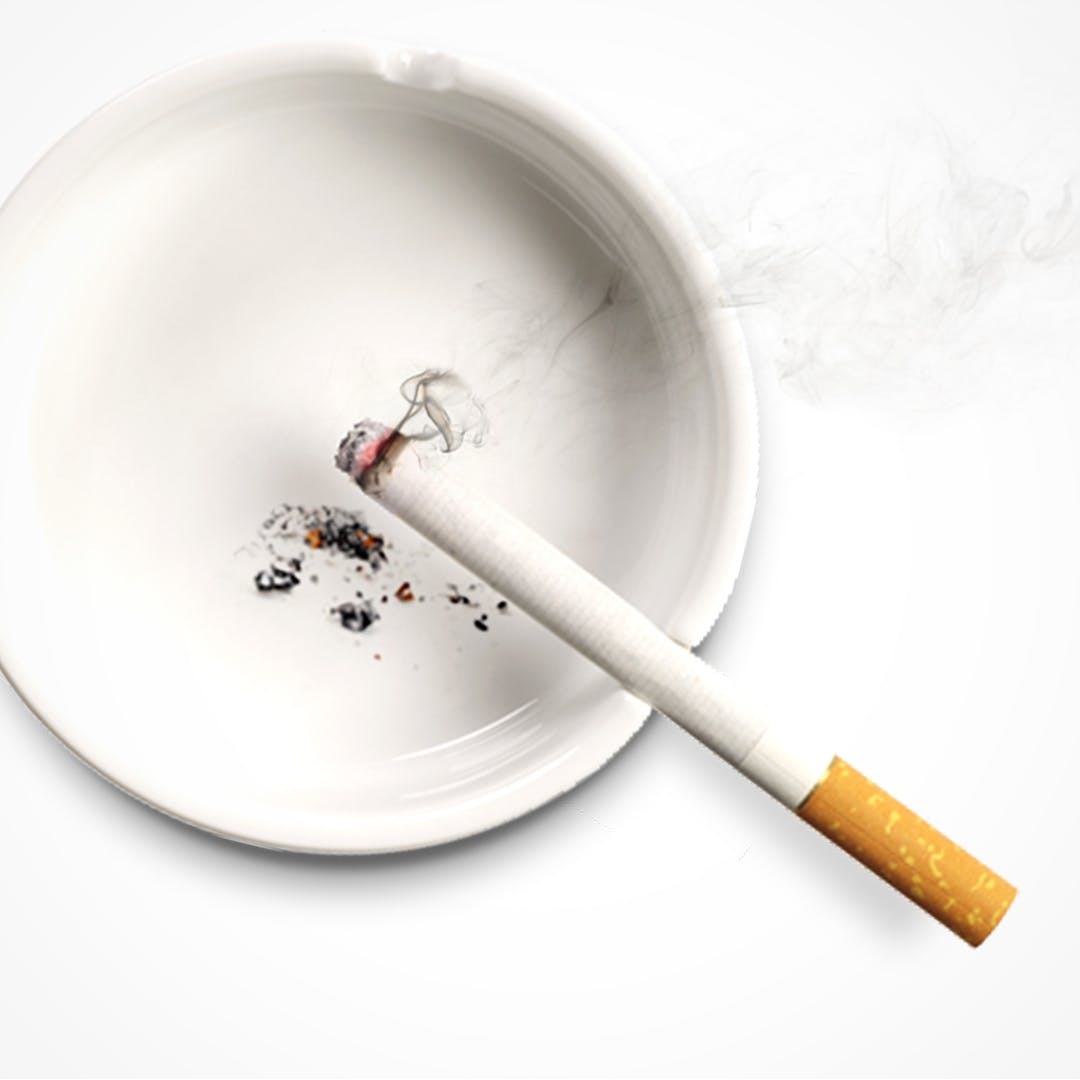 Zapálená cigareta opřená v popelníku