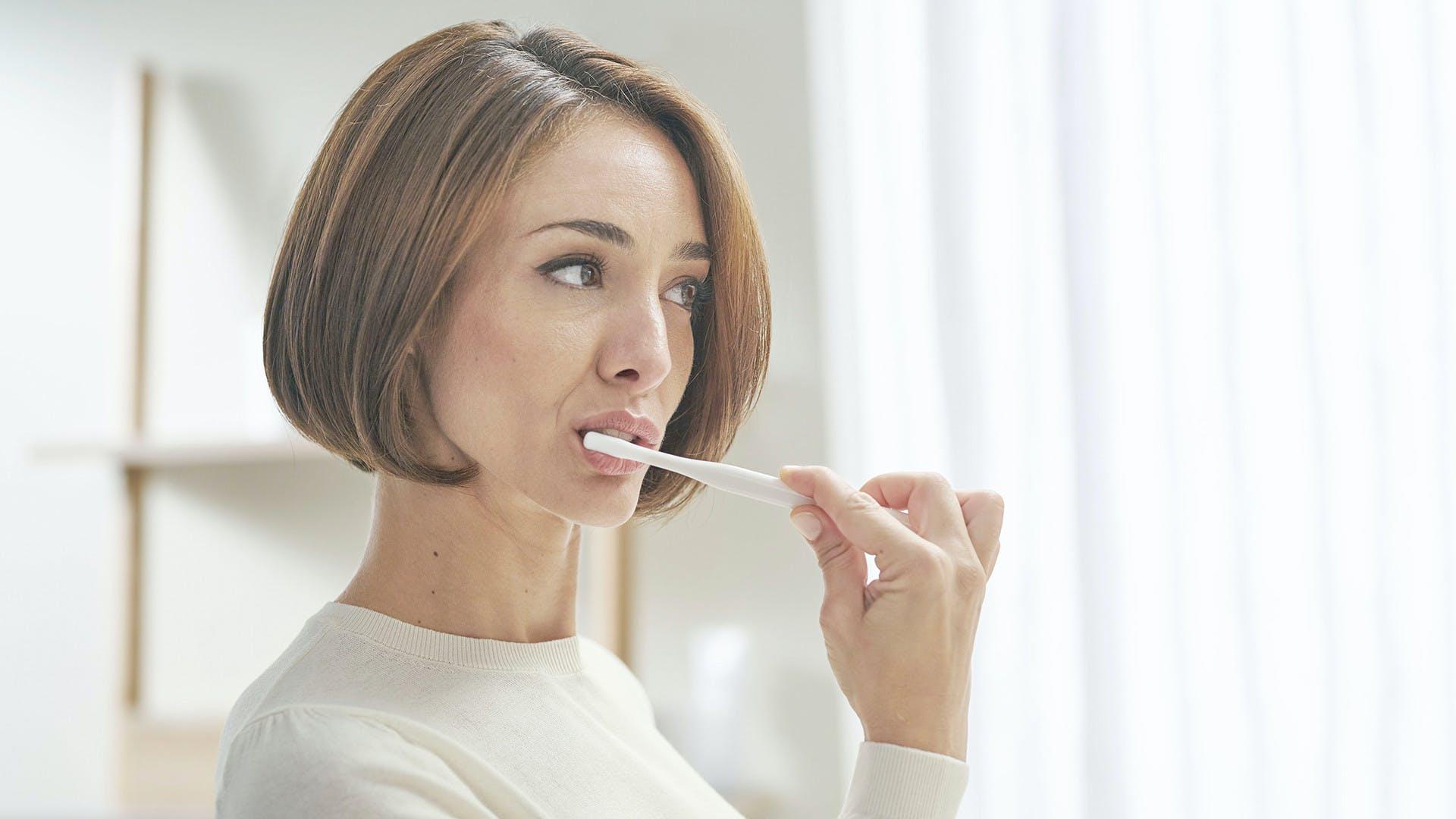 Žena, která si zuby čistí zubní pastou Parodontax Kompletní ochrana