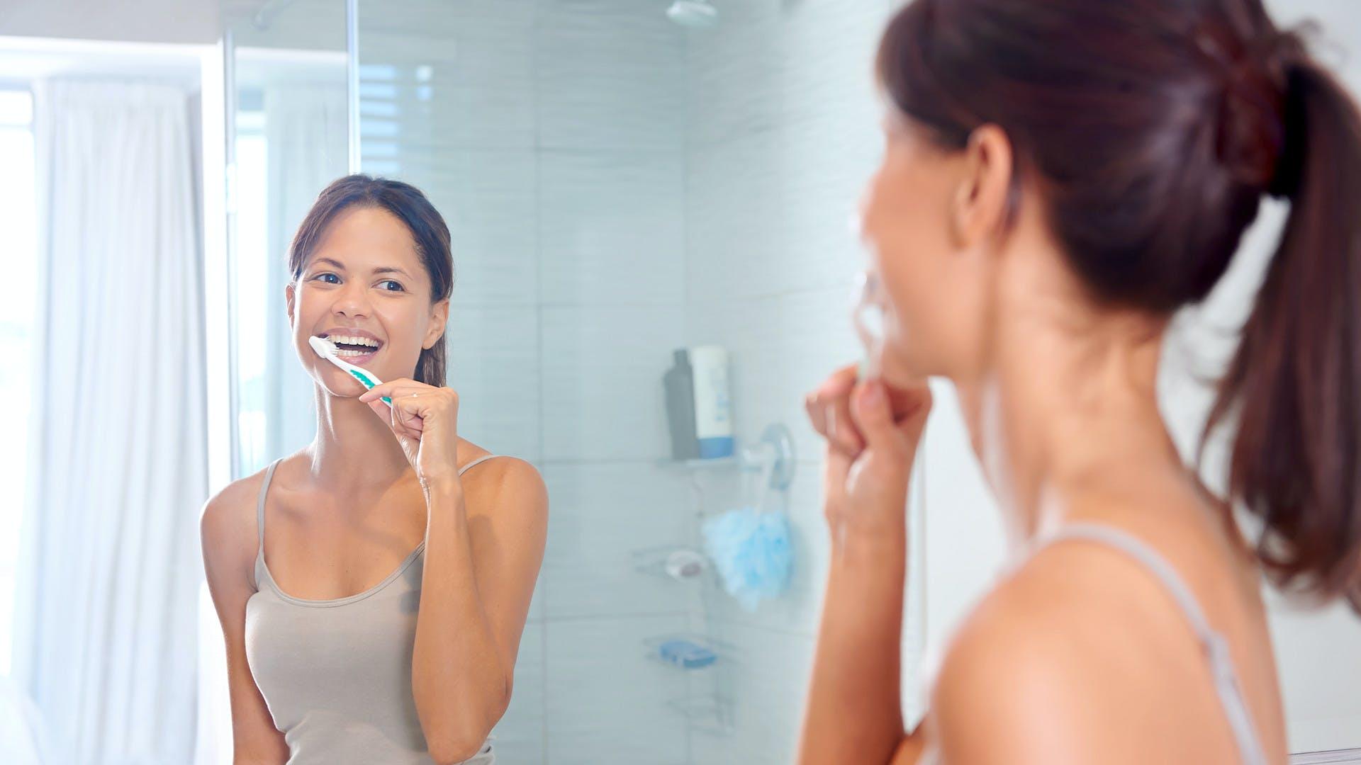 Žena, která si súsměvem čistí zuby